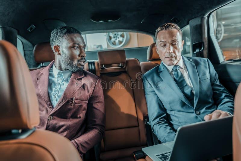 Dois homens que sentam-se no assento traseiro do carro imagens de stock royalty free