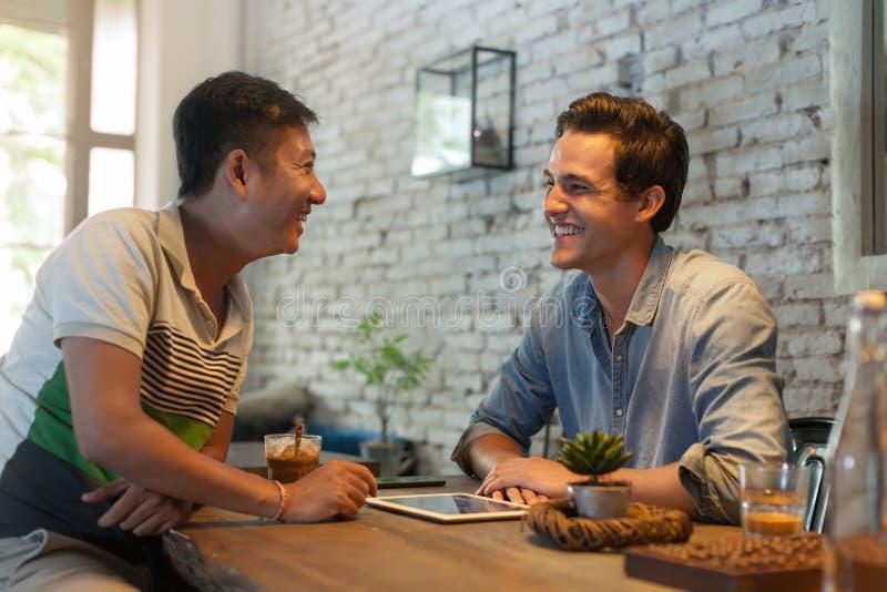 Dois homens que sentam-se no café, amigos asiáticos da raça da mistura fotografia de stock