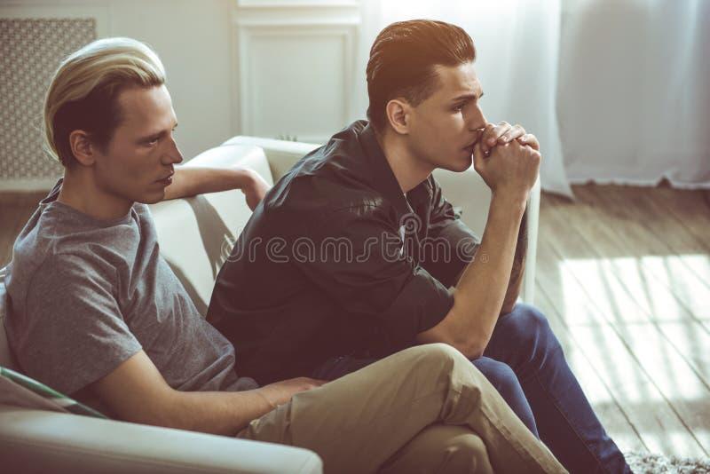 Dois homens sérios novos que sentam-se no sofá em casa imagem de stock