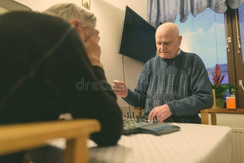 Dois homens sêniores jogando xadrez enquanto relaxavam em uma casa de repouso em Turku, Finlândia imagem de stock