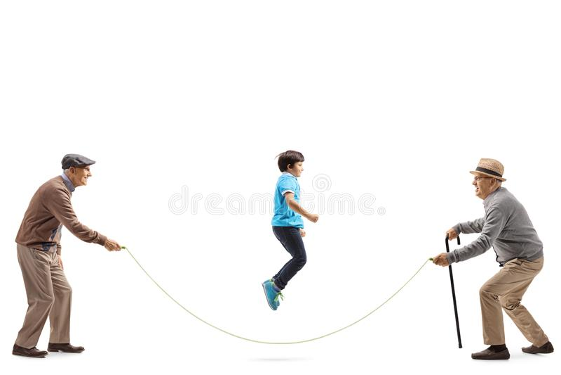Dois homens superiores que guardam uma corda e um salto do menino fotos de stock
