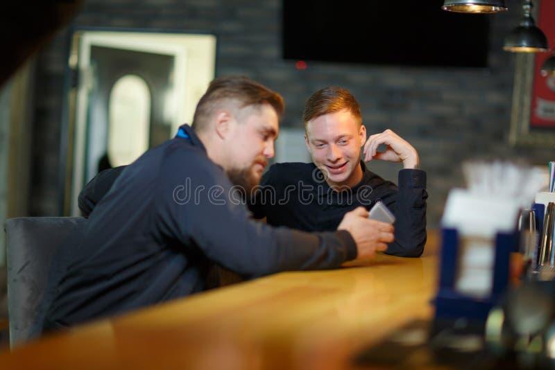 Dois homens, têm uma conversação, contemplando um smartphone moderno que senta-se em uma barra fotos de stock