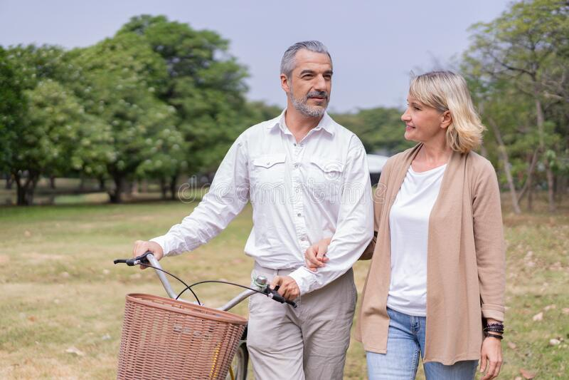 Dois idosos relaxando no parque andando com bicicleta e conversando juntos de manhã O conceito de boa saúde e relaxamento imagens de stock