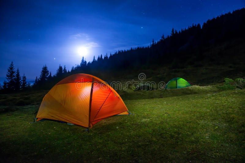 Dois iluminaram barracas de acampamento alaranjadas e verdes foto de stock