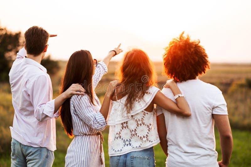 Dois indivíduos novos e duas meninas vestidos no roupa à moda estão estando no campo e estão olhando na frente deles na imagem de stock