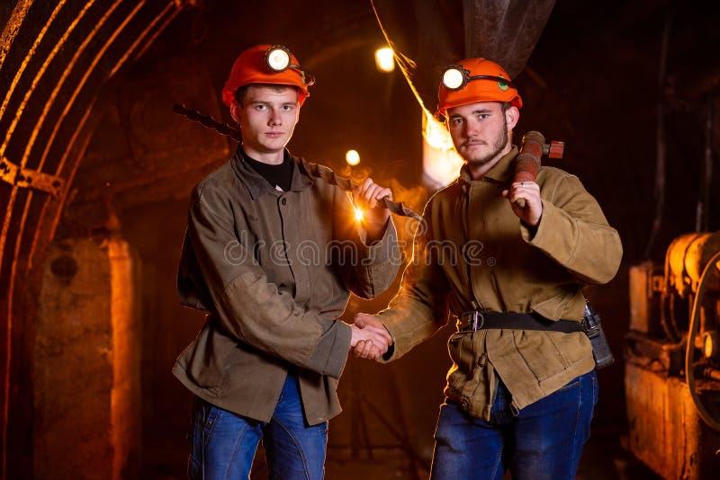 Dois indiv?duos novos em trabalhar os capacetes uniformes e protetores, agitando as m?os fotografia de stock royalty free