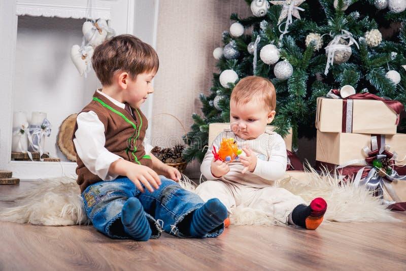 Dois irmãos em antecipação ao Natal na árvore de Natal imagem de stock royalty free