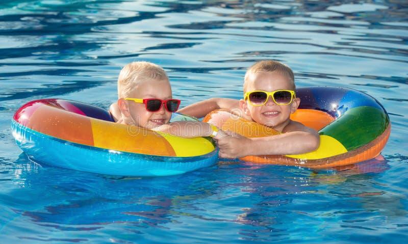 Dois irmãos em círculos nadadores infláveis na associação no dia de verão quente Jogo de crianças no recurso tropical Férias da p imagem de stock royalty free