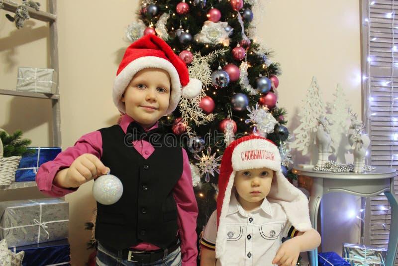 Dois irmãos em chapéus do Natal fotografia de stock