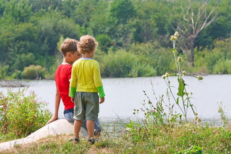 Dois irmãos estão sentando-se ao ar livre fotografia de stock
