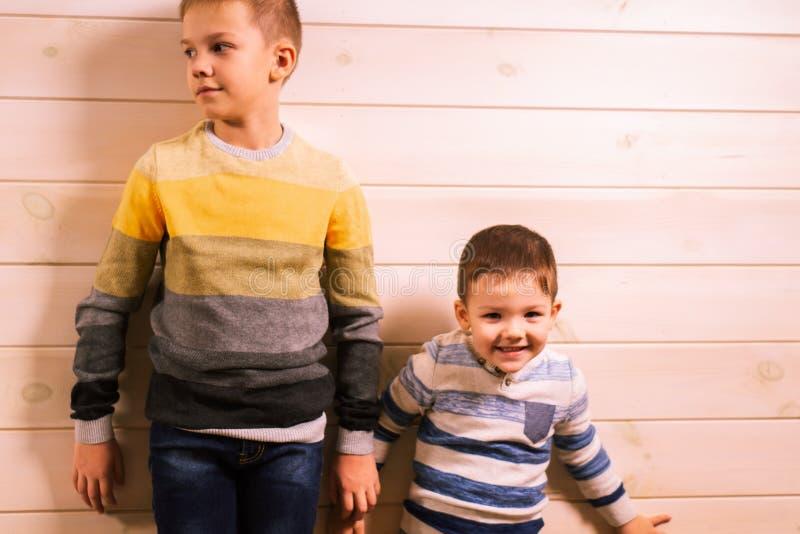 Dois irmãos - irmão mais velho e irmão mais novo, falando na casa na perspectiva de uma parede de madeira branca imagens de stock