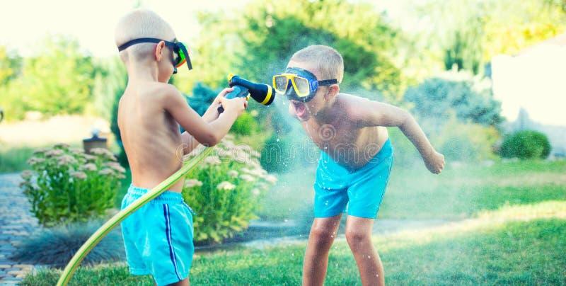 Dois irmãos jogam em um dia quente do verão no jardim As crianças estão espirrando com uma mangueira de jardim foto de stock