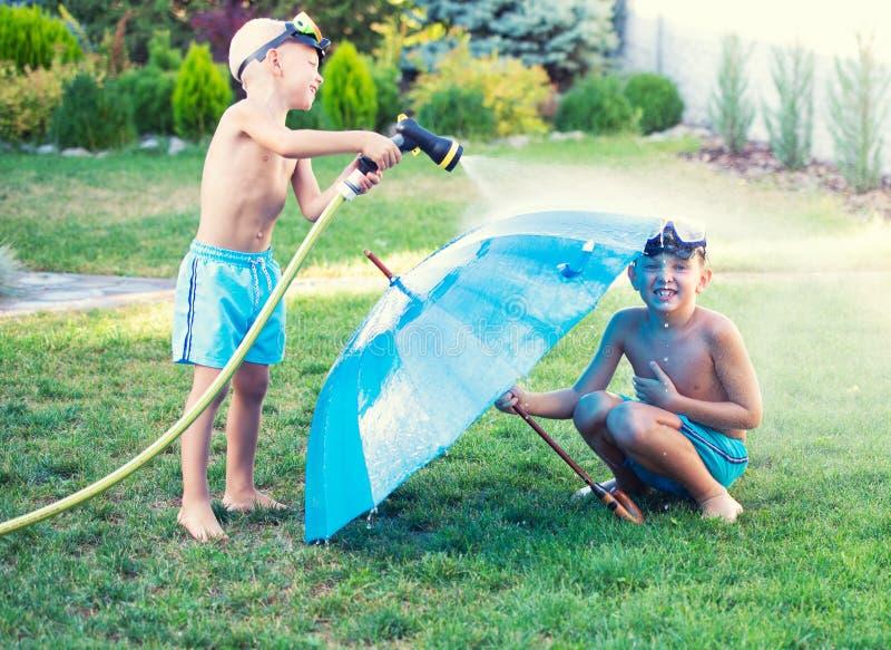 Dois irmãos jogam em um dia quente do verão no jardim As crianças estão espirrando com uma mangueira de jardim fotografia de stock royalty free