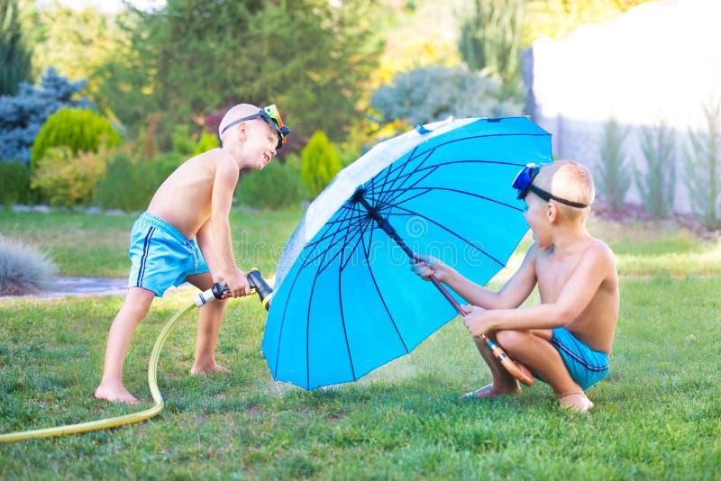 Dois irmãos jogam em um dia quente do verão no jardim As crianças estão espirrando com uma mangueira de jardim imagem de stock royalty free