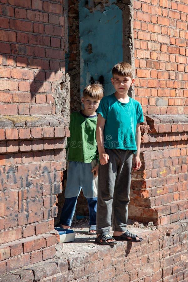 Dois irmãos mais novo são órfão, vivendo em uma casa abandonada e abandonada, crianças da guerra Foto encenada fotografia de stock