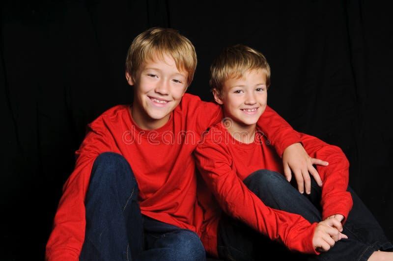 Dois irmãos na camisa vermelha no fundo preto foto de stock