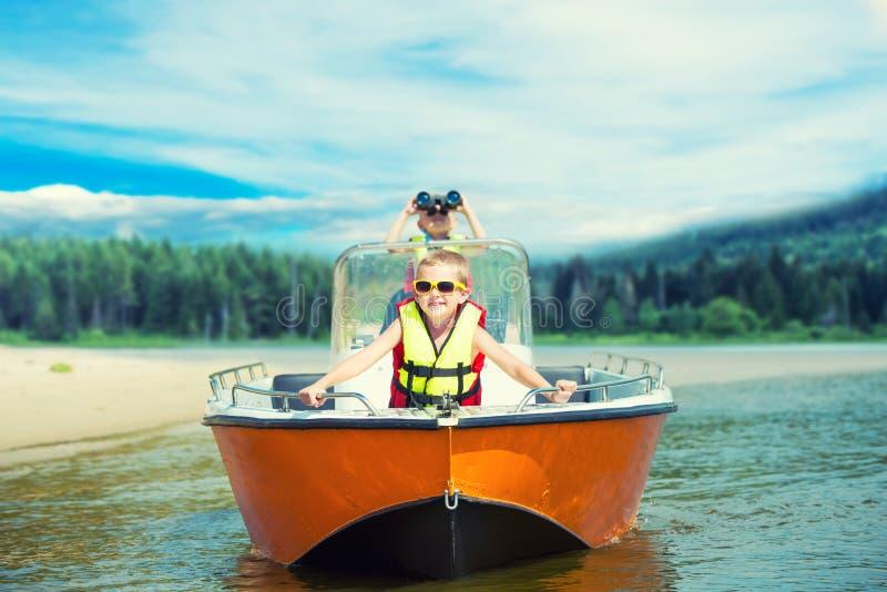Dois irmãos nadam em um barco de motor no lago fotografia de stock royalty free