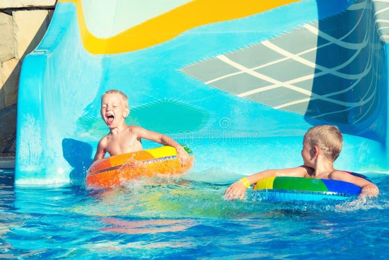 Dois irmãos no círculos de borracha infláveis para guardar as mãos e abaixar a corrediça de água fotografia de stock