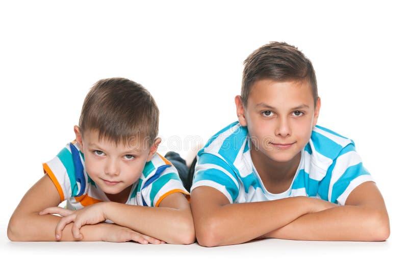 Dois irmãos pensativos no assoalho imagens de stock