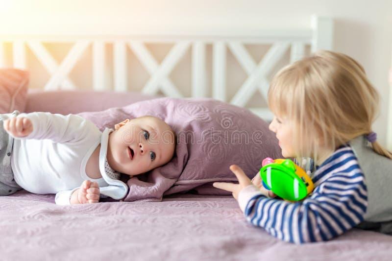 Dois irmãos pequenos bonitos que jogam junto na cama Irmã e irmão que têm o divertimento no quarto na manhã Família feliz com imagem de stock royalty free