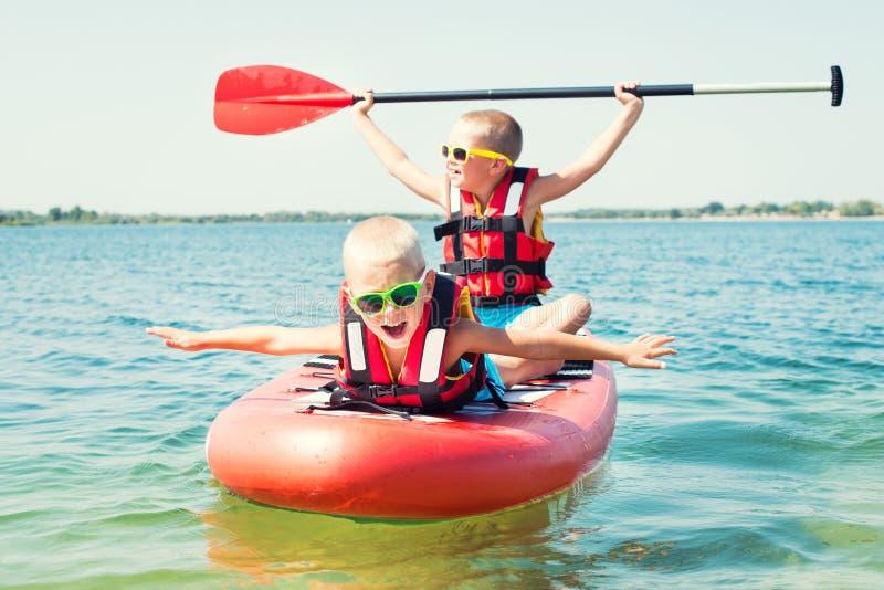 Dois irmãos que nadam sobre levantam-se a placa de pá Esportes de água, estilo de vida ativo fotos de stock royalty free