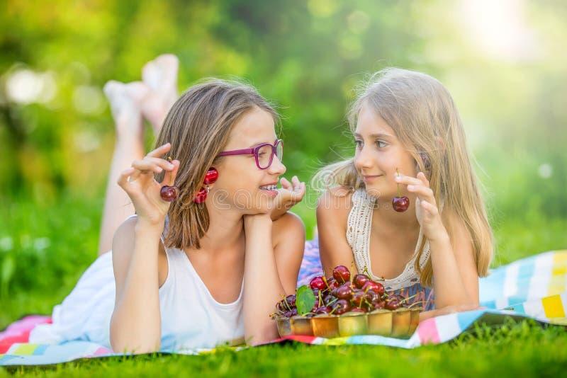 Dois irmãs ou amigos bonitos em um jardim do piquenique encontram-se em uma plataforma e comem-se cerejas recentemente escolhidas fotografia de stock
