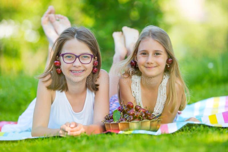 Dois irmãs ou amigos bonitos em um jardim do piquenique encontram-se em uma plataforma e comem-se cerejas recentemente escolhidas fotografia de stock royalty free