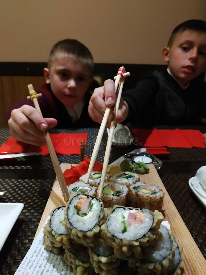Dois irm?os comem rolos de sushi em casa imagens de stock royalty free