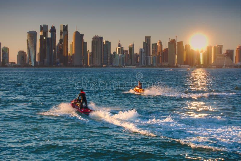 Dois jato-esquis que cruzam com a skyline da baía ocidental no fundo, no por do sol Doha, Qatar fotos de stock royalty free