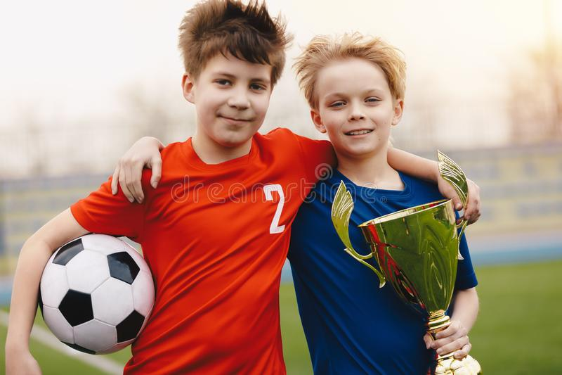 Dois jogadores de futebol felizes dos meninos que guardam a bola de futebol e o troféu dourado imagens de stock
