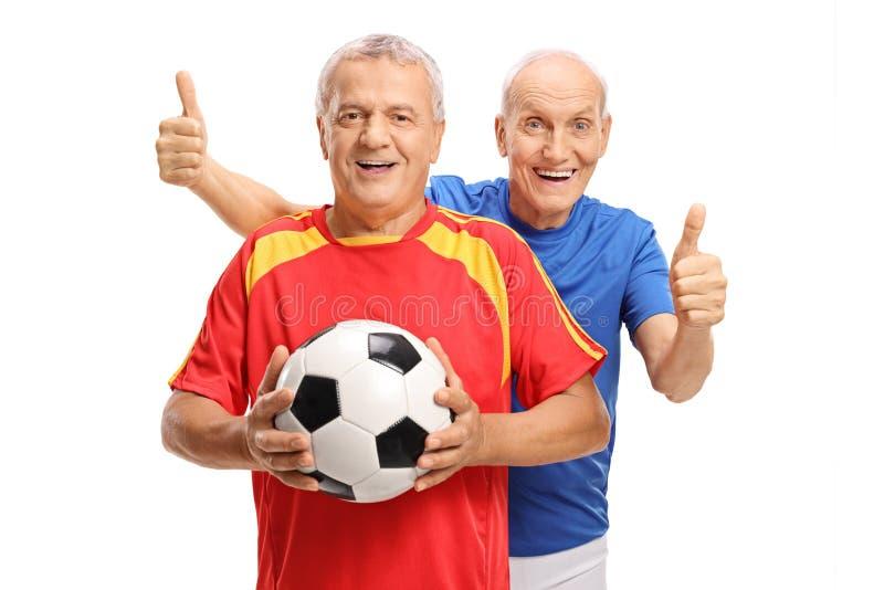 Dois jogadores de futebol idosos alegres com futebol e polegares acima imagem de stock royalty free