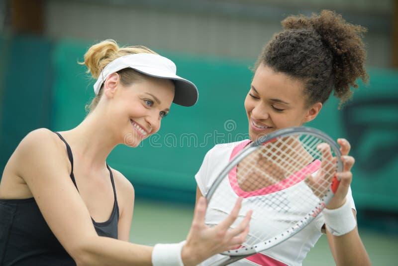 Dois jogadores de tênis fêmeas bonitos que guardam o sorriso da raquete fotografia de stock