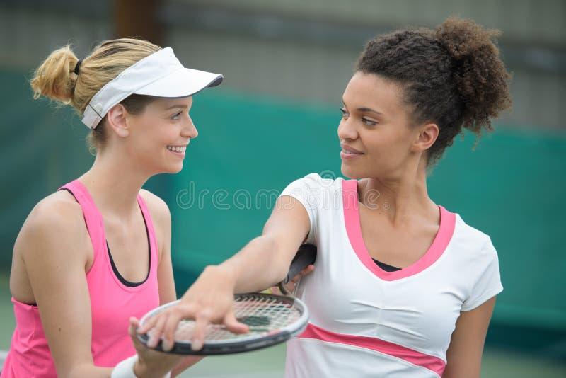 Dois jogadores de tênis fêmeas bonitos que guardam raquetes fotografia de stock