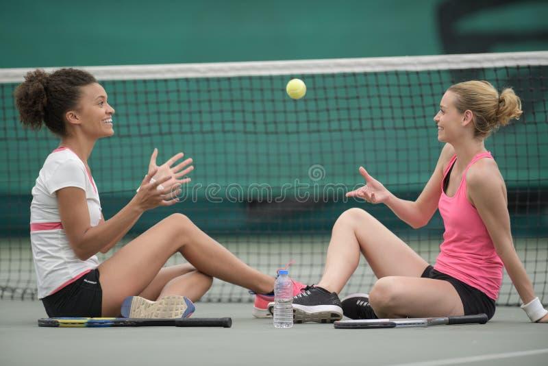 Dois jogadores de tênis fêmeas que sentam-se junto na corte imagens de stock