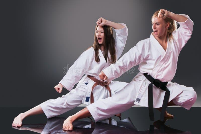 Dois jogadores fêmeas novos bonitos do karaté que fazem o kata no fundo cinzento fotos de stock