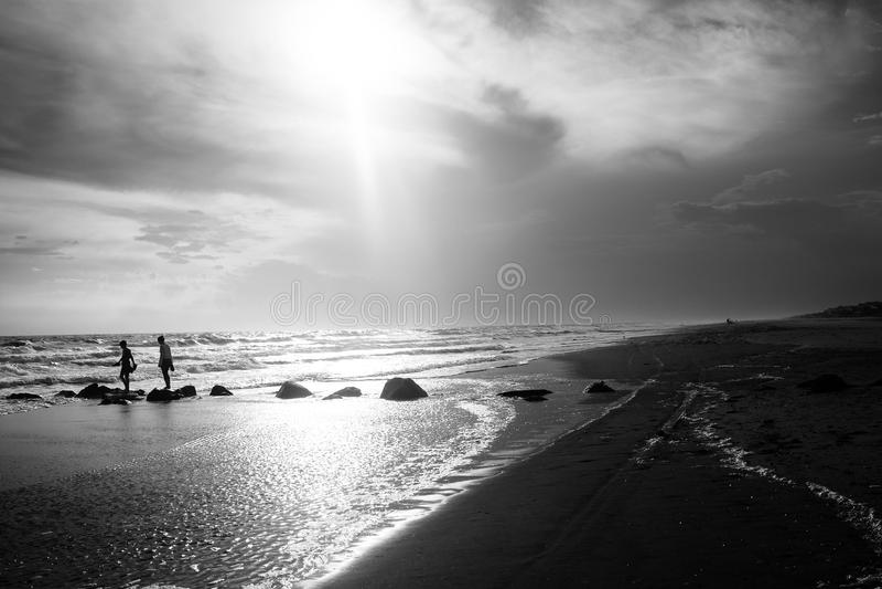 Dois jovens andam ao longo de um molhe para fora ao mar imagem de stock