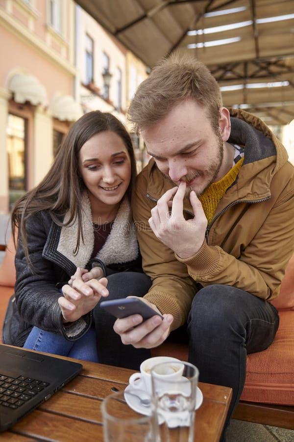 Dois jovens, 20-29 anos velhos, sentando-se no café junto, usando o smartphone no café fotografia de stock