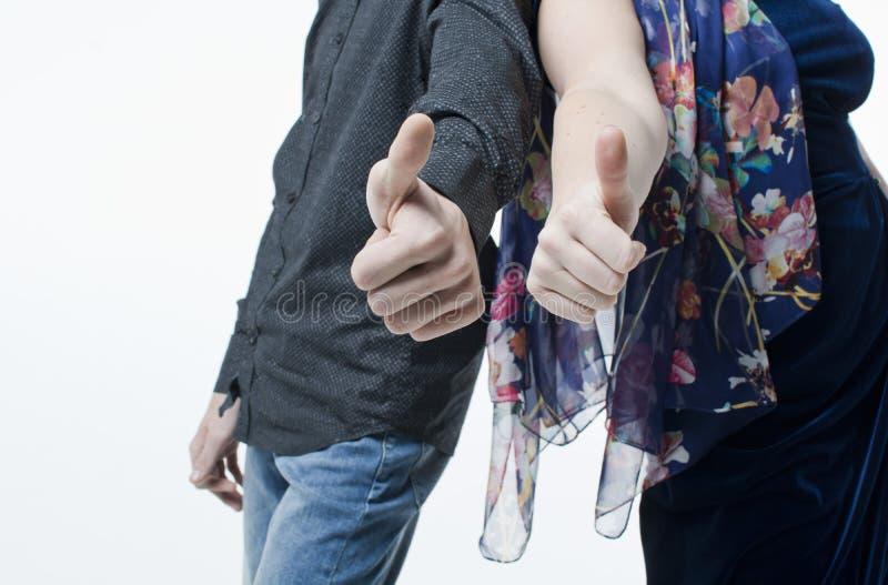 Dois jovens, o homem e as mulheres, dedos com símbolo gostam imagens de stock