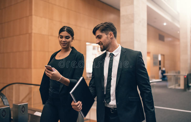 Dois jovens que andam junto no terminal de aeroporto imagens de stock