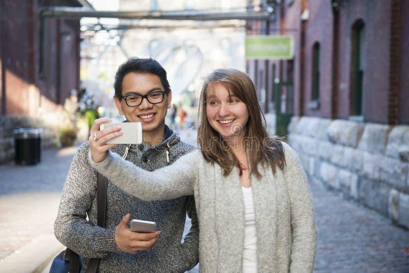 Dois jovens que tomam um selfie com smartphone imagem de stock