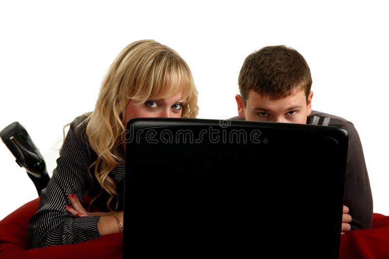 Dois jovens que trabalham em um encontro do portátil imagem de stock