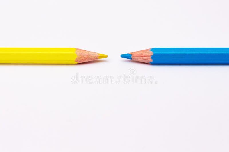 Dois lápis de amarelo e de azul, simbolizam o opposite_ foto de stock royalty free