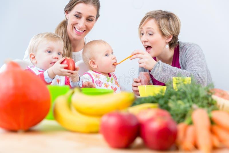 Dois mães e melhores amigos felizes que sorriem ao alimentar seus bebês imagens de stock royalty free