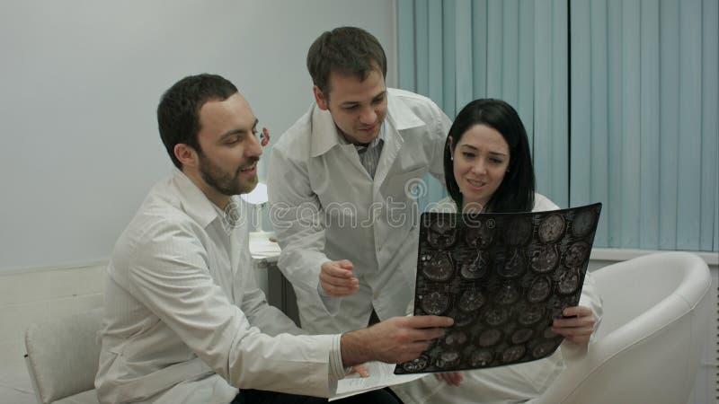 Dois médicos no bom humor analisam resultados do paciente para diagnosticar a doença, a seguir vêm interno com raio X foto de stock