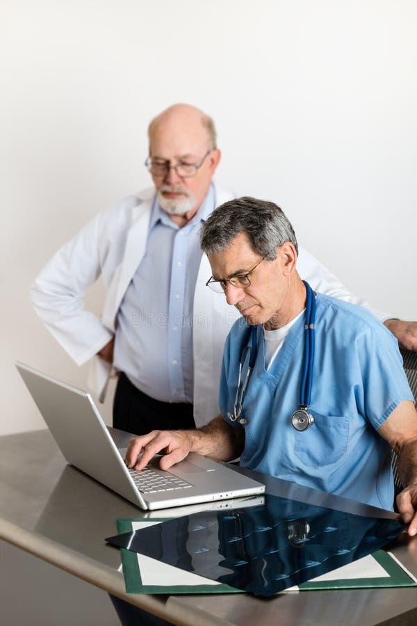 Dois médicos superiores que discutem varreduras do filme do MRI do paciente foto de stock