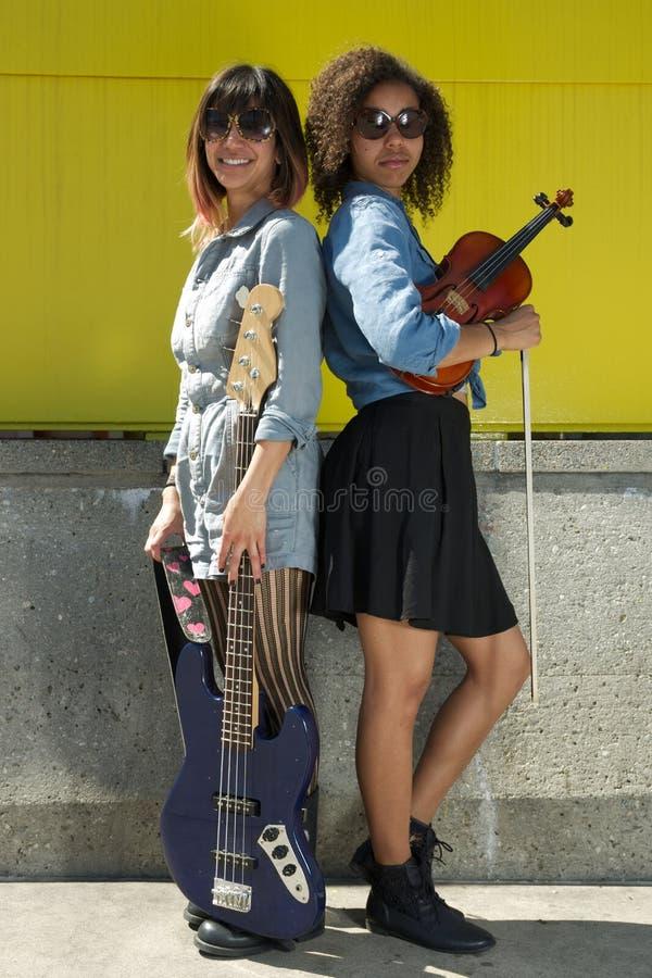 Dois músicos fêmeas que estão de volta à parte traseira que guarda instrumentos imagens de stock