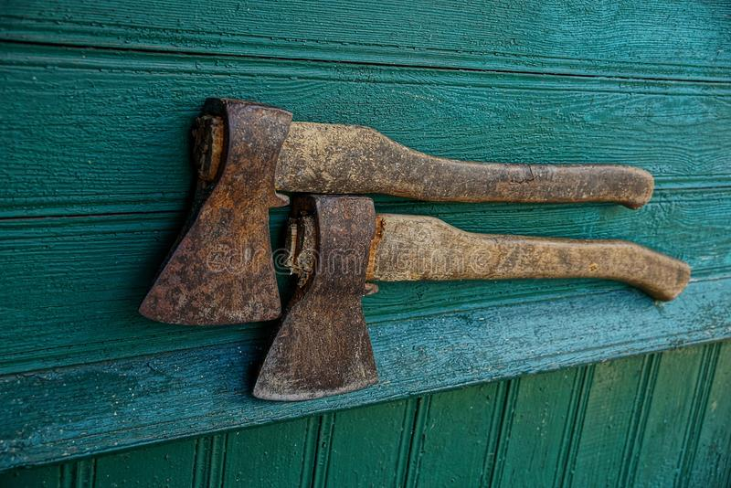 Dois machados velhos na parede da casa verde embarcam imagens de stock royalty free