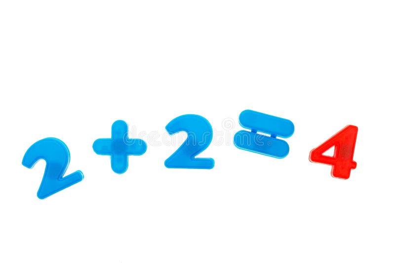 Dois mais dois são iguais a quatro dos ímãs coloridos dos números isolados no fundo branco Conceito da matemática imagens de stock