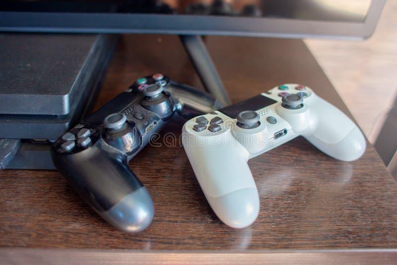 Dois manches do console do jogo - chery e branco - mentira em uma tabela perto da tevê e do console do jogo imagem de stock royalty free