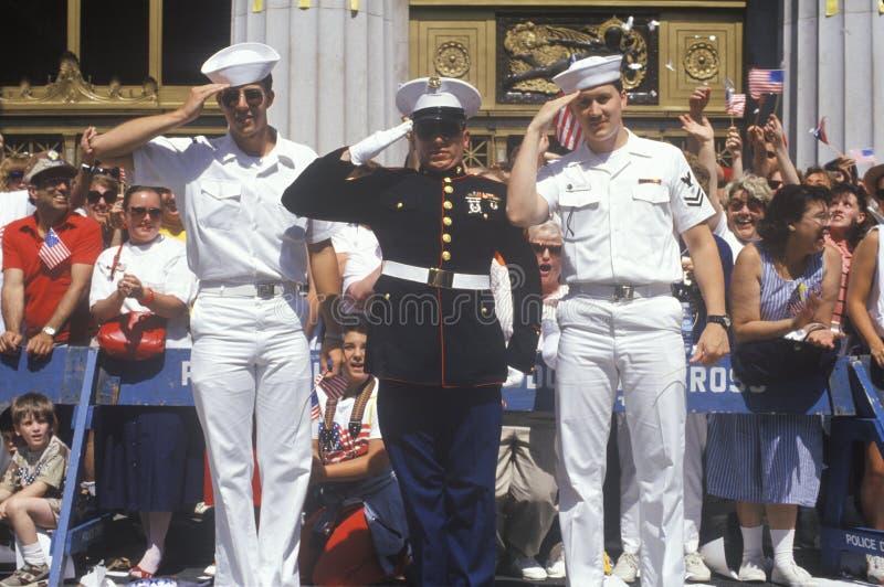 Dois marinheiros americanos e um Estados Unidos Marine Saluting na parada, América foto de stock